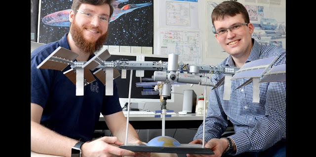 Claas Olthoff (left) and Daniel Pütz with a model of the International Space Station. (Photo: Stefanie Reiffert / TUM)