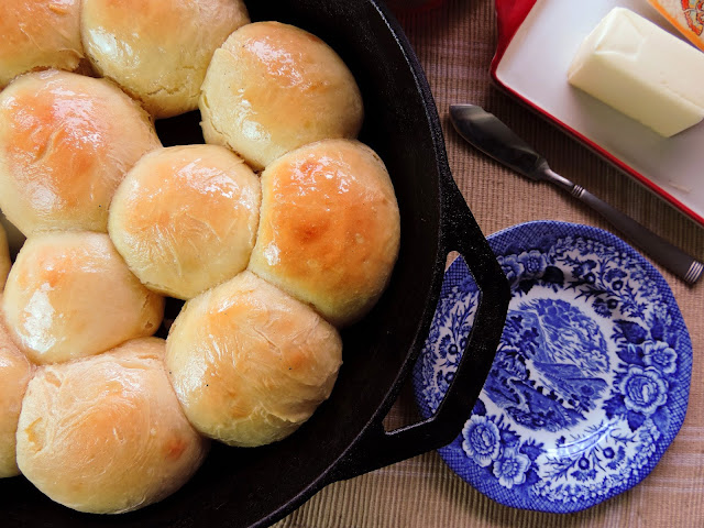 The finished homemade dinner rolls, in a cast iron skillet, ready to eat.