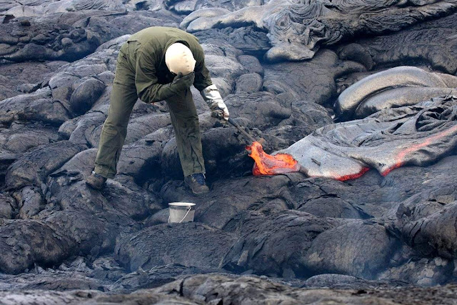 A geologist is collecting sample of molten lava from 2011 Kamoamoa eruption, at Kilauea Volcano, Hawaii, U.S.