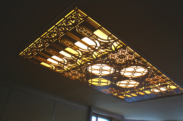 Use of screens and geometric patterns in Frank Lloyd Wright's lighting fixtures.