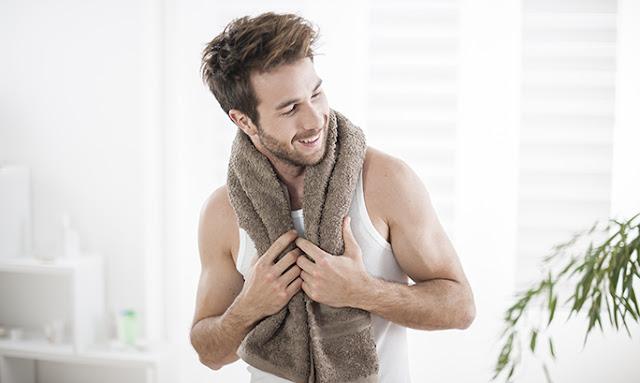 Νέος άντρας με λευκό φανελάκι και καφέ πετσέτα στο λαιμό Ομορφιά Η απαραίτητη περιποίηση για τους άντρες