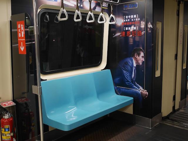 movie promotion on Taipei Metro train with image of Liam Neeson sitting next to real seats