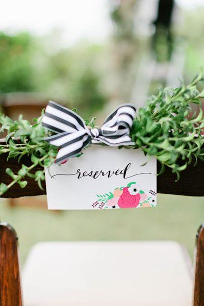 Tarjeta identificadora de asiento decorada con ramillete vegetal y lazo