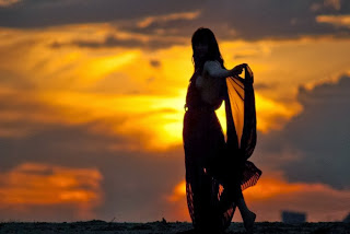 Γυναίκα με πέπλο ατενίζει το ηλιοβασίλεμα.