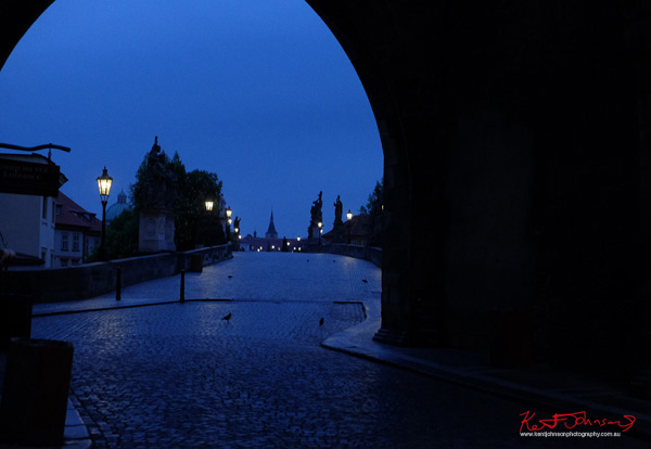 Looking through the arch of the tower to the new town. The Charles Bridge in Spring Prague by Travel and Lifestyle Photographer Kent Johnson.