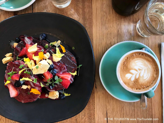 A flat white espresso drink in a green cup and velvet pancakes decorated with sliced strawberries and edible flowers
