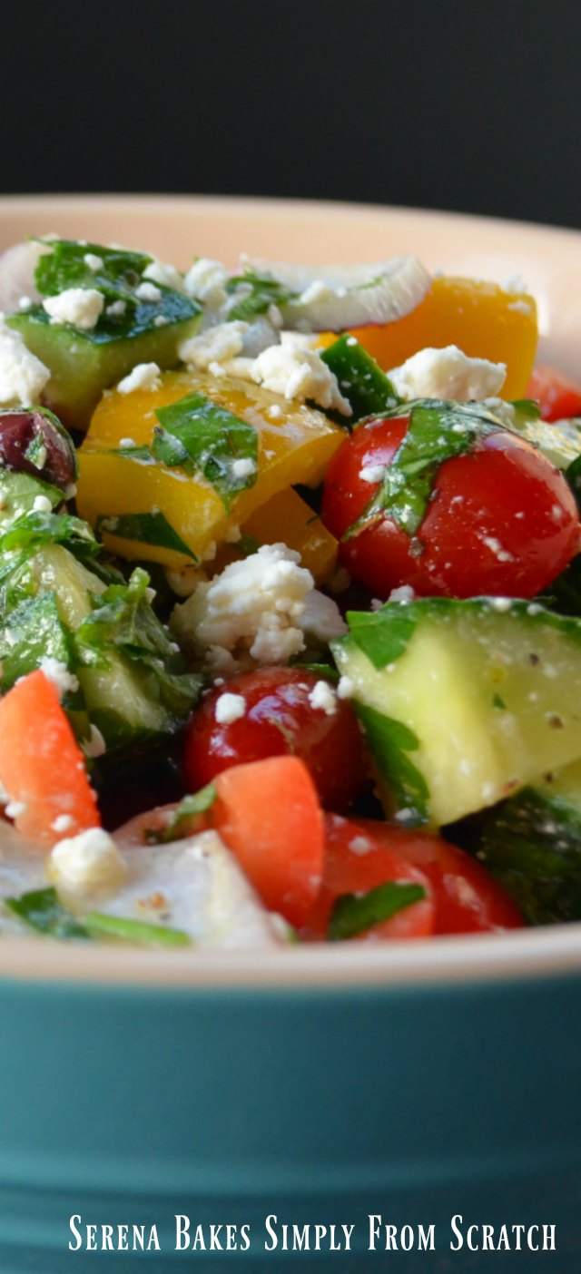 A cream colored bowl on the inside and turquoise on the outside filled with Greek Salad with cherry tomatoes, chopped cucumber, chopped bell pepper, kalamata olives, parsley, and sprinkled with feta cheese.