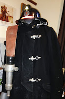 A heavy dark coat with 3 metal clasps, helmet, pants and boots, and a fire hose draped over shoulder.