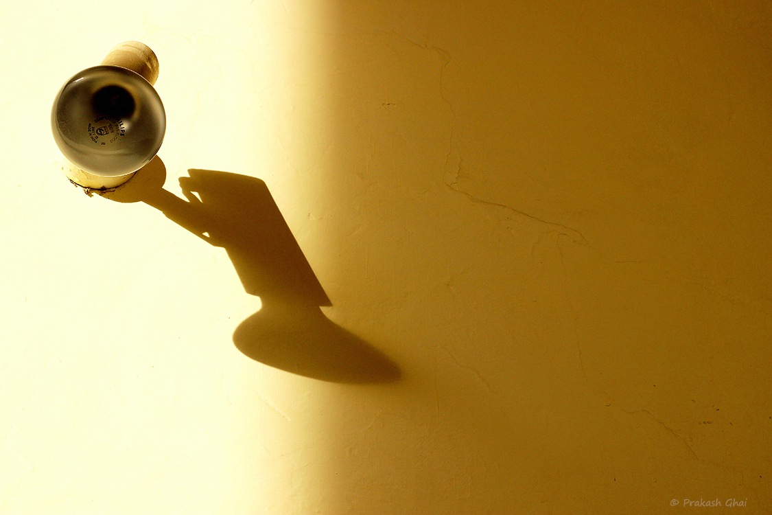 A Minimalist Photo of Long shadow of a wall mounted light bulb.