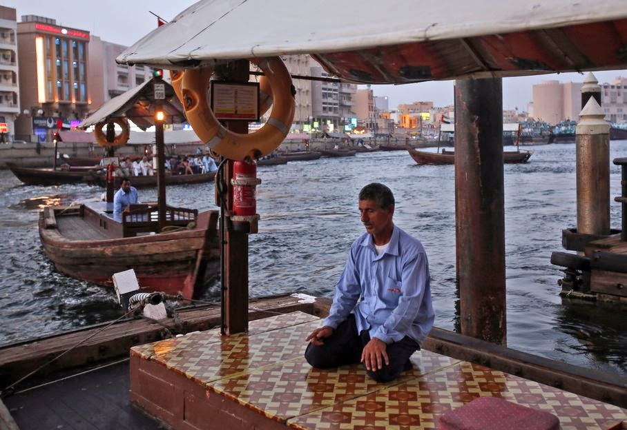 In this Tuesday, May 27, 2014 photo, an abra, or boat taxi, driver performs the evening payers on his boat at the creek in Dubai, United Arab Emirates. Beneath a glitzy skyline wooden boats ply Dubai Creek, the historic heart of a city that was transformed in little more than a generation from a tiny pearling and fishing port to a global trading hub.