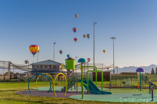 Cramer Imaging's fine art photograph of lots of hot air balloons taking flight in Panguitch Utah over playground equipment and a baseball field