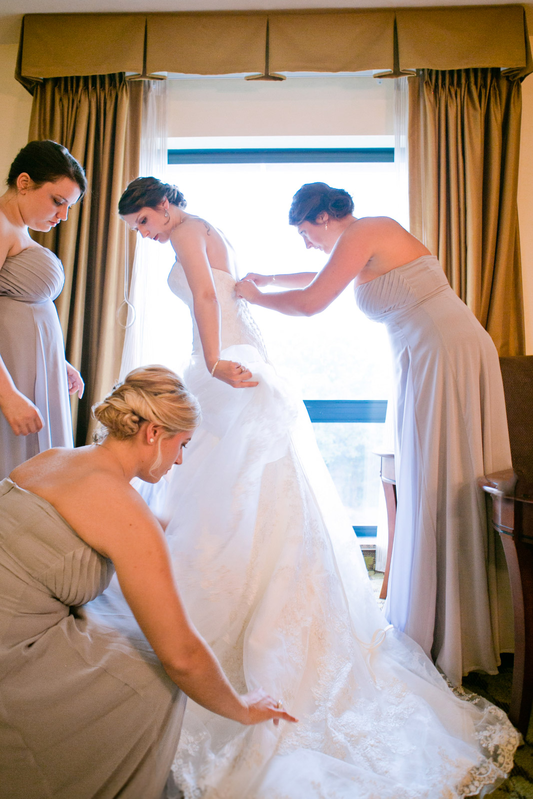 the bridesmaids surround the bride to assist her with her wedding dress before the wedding