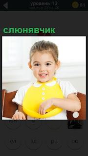 На ребенке одет желтого цвета слюнявчик, она сидит за столом