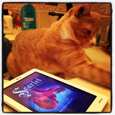 A ginger cat, Ollie, sits in a sink. One paw reaches out to grasp something outside the shot. On the counter beside him is a white Kobo with Scarlet's cover on its screen.  The cover features a swirl of red cloak and a flash of red hair against a dark blue background.