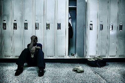 Teenager sitting on the floor beside his opened locker
