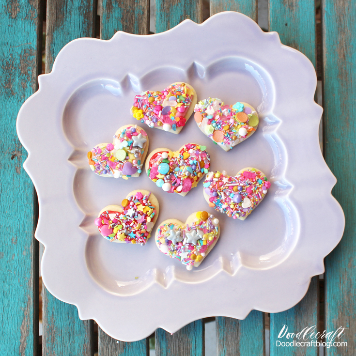 Brightly colored sprinkles pressed onto heart shaped cookies.