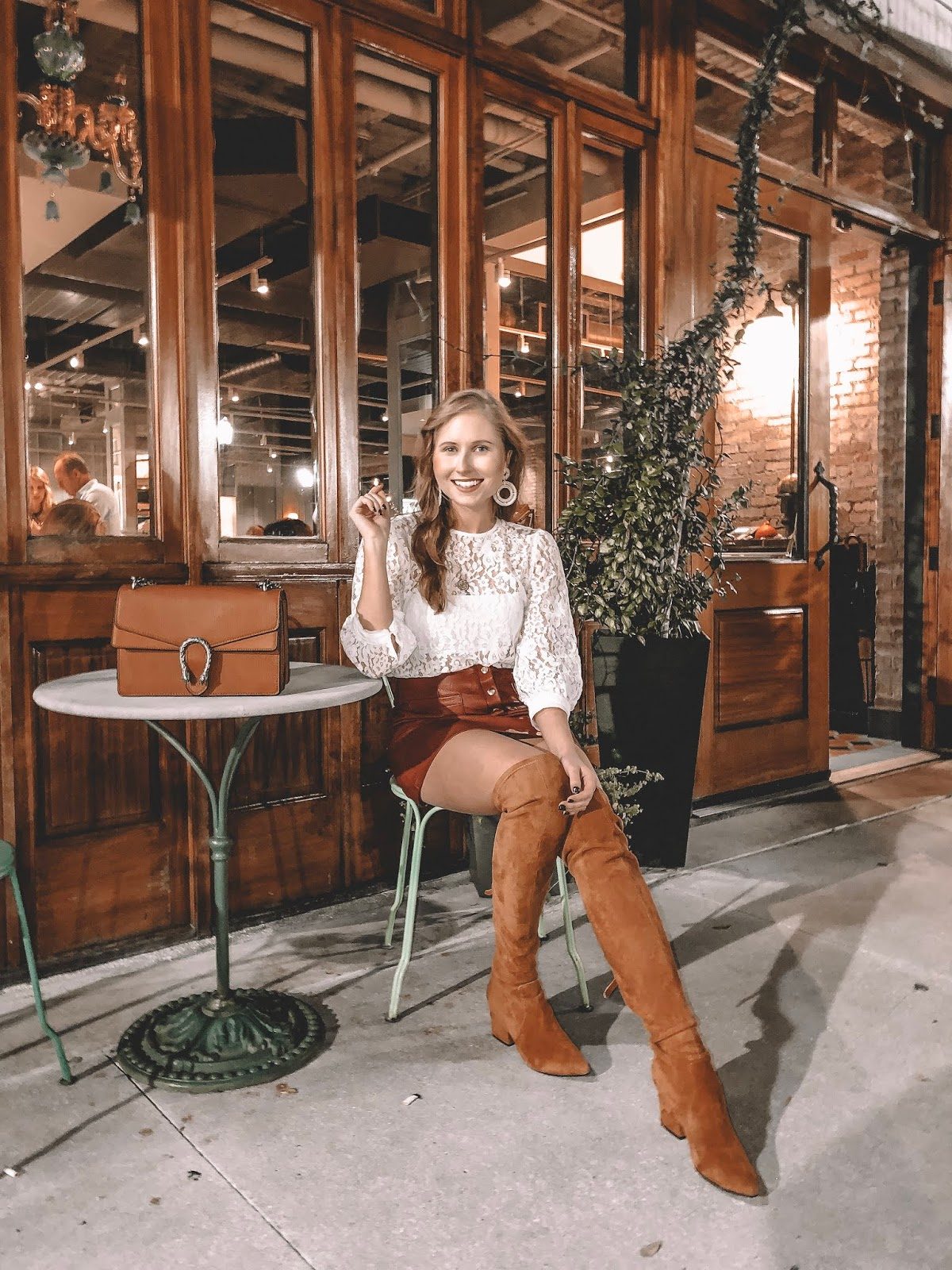 Tampa blogger Amanda Burrows sits outside the restaurant On Swann in Hyde Park Village wearing over the knee boots from Goodnight Macaroon in the evening.