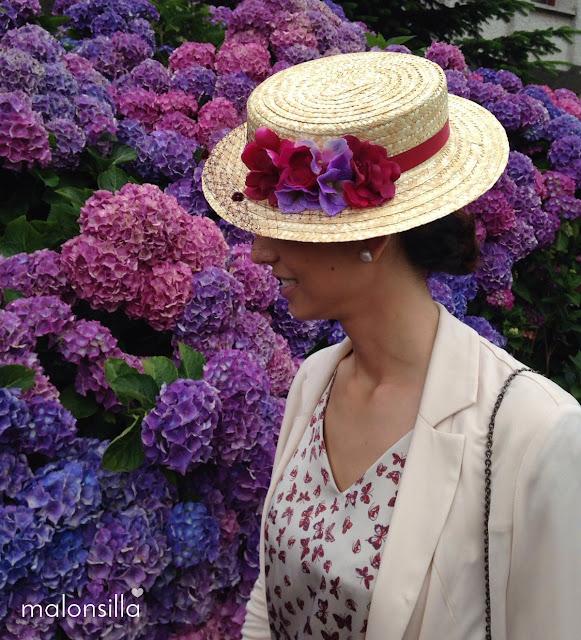 Look invitada de perfil con vestido de mariposas, chaqueta beig y canotier Luanco en burdeos de copa baja, fondo de flores de hortensia