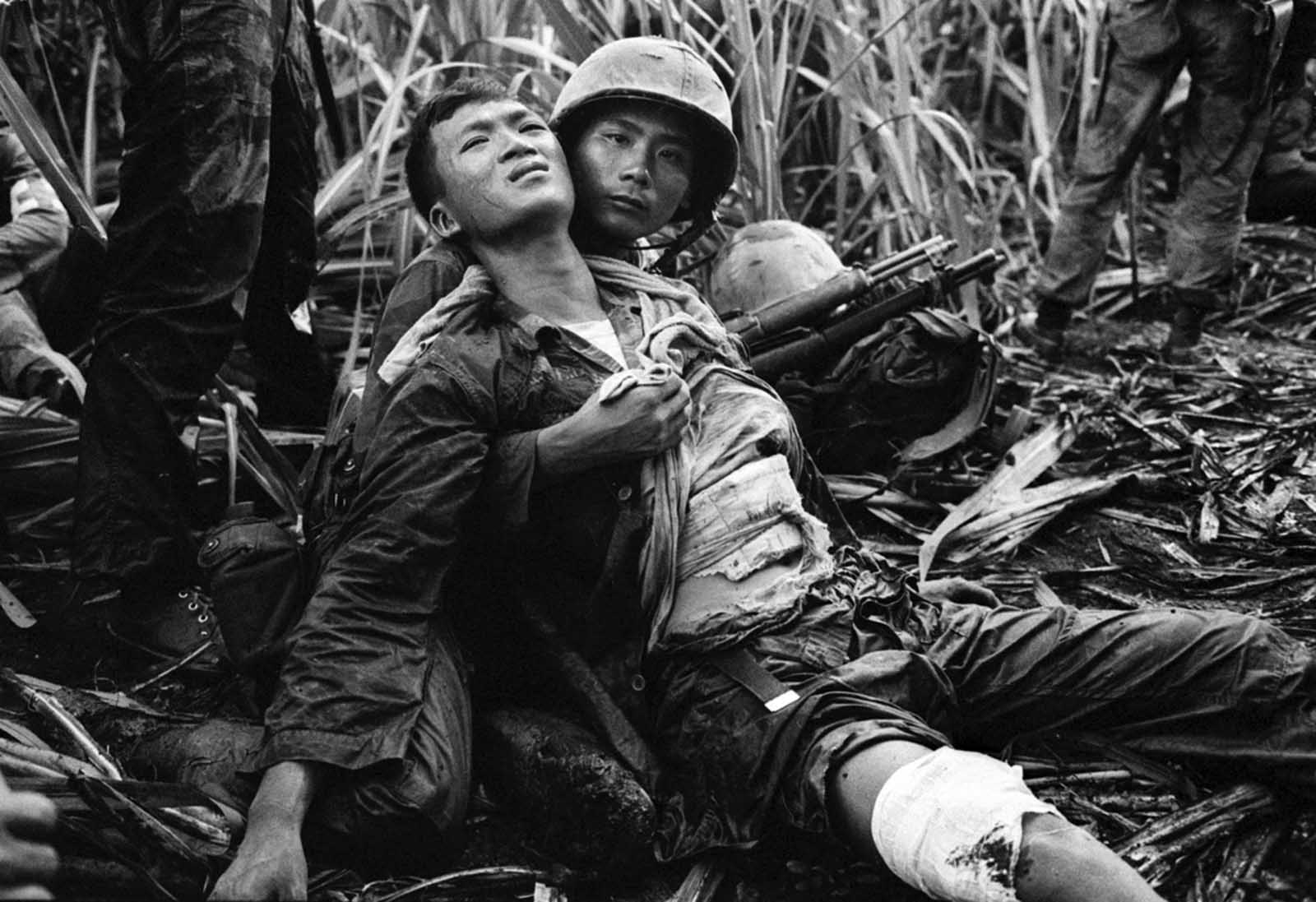 A South Vietnamese Marine, severely wounded in a Viet Cong ambush, is comforted by a comrade in a sugar-cane field at Duc Hoa, about 12 miles from Saigon, on August 5, 1963. A platoon of 30 Vietnamese Marines was searching for communist guerrillas when a long burst of automatic fire killed one Marine and wounded four others.