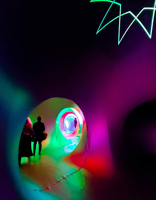 Interior of inflatable art sculpture with people walking through multi-colored tunnels