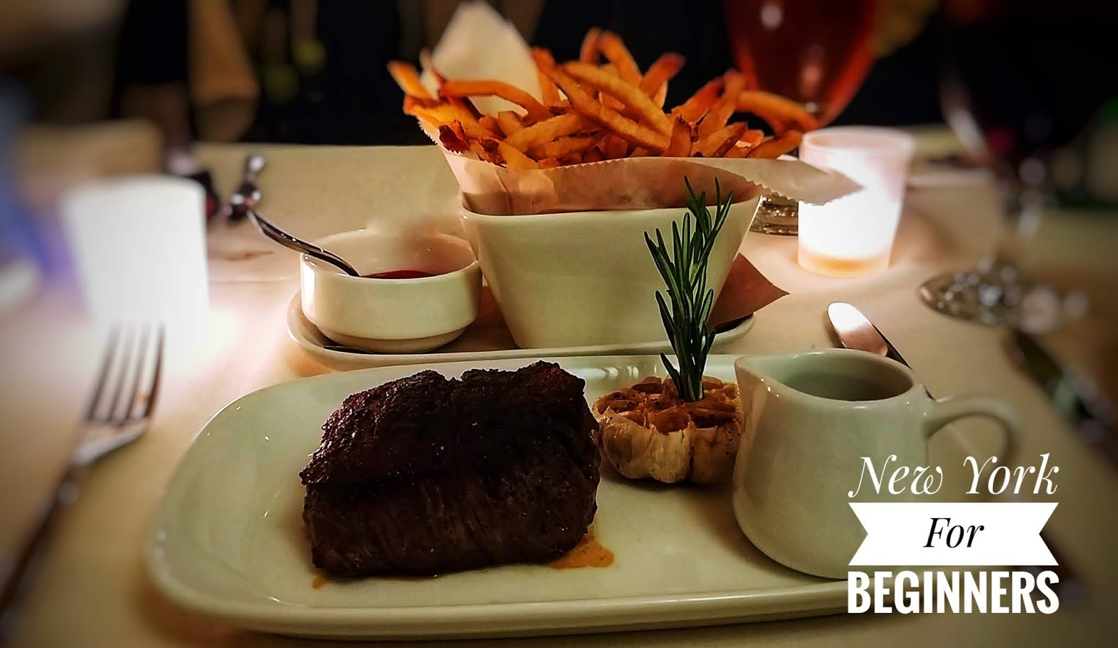Image of a black angus filet mignon with a jar of sauce and french fries