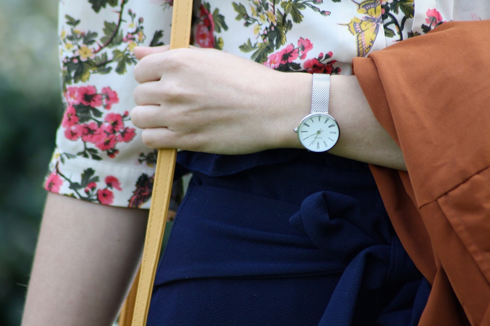 A close up taken at waist level, showing Abbey's floral top, blue trousers, tan coat, and silver watch