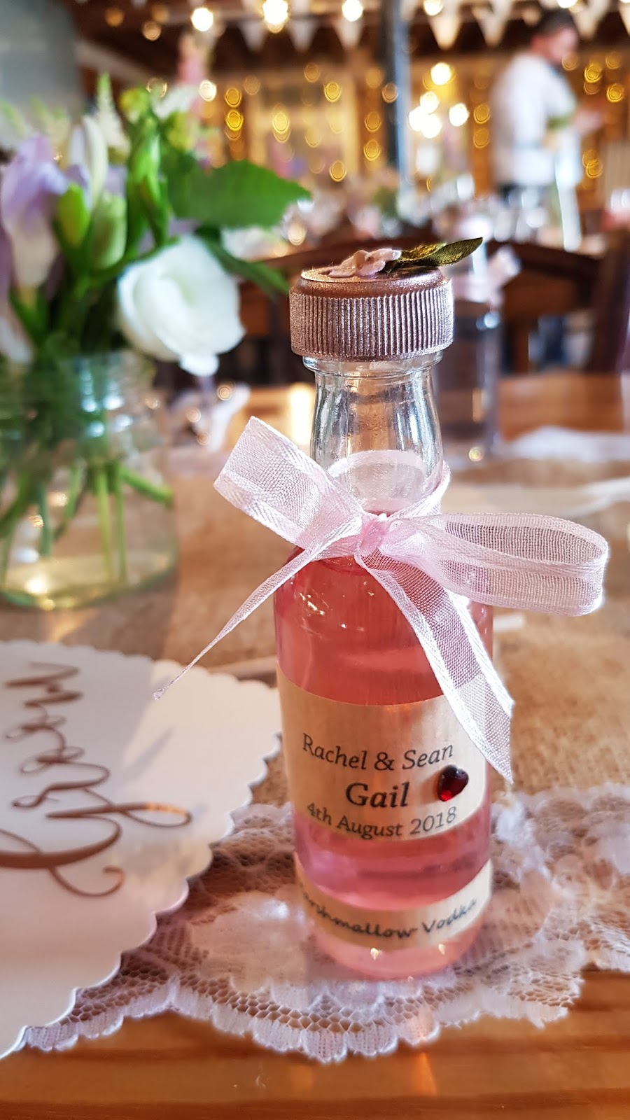 A different way of directing guests to their seats at a wedding:  miniature bottles of home made vodka with the bride and groom's name