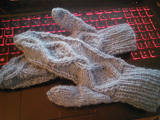 Two cabled mittens laying on top of one another, knit in a pale blue dk-weight yarn.