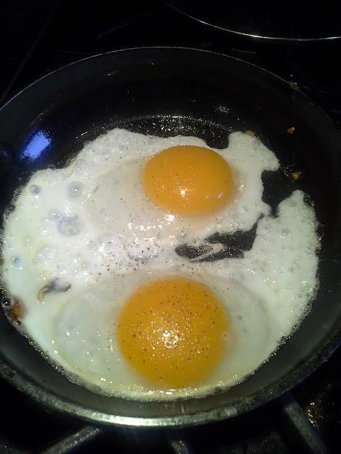frying dug eggs in skillet