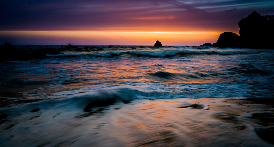 The rich colors of the setting sun cover the sky, and reflect as a blanket of colors on the Pacific ocean at DeMartin Beach in Northern California