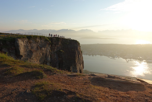 people on a cliff overlooking city of Tromso during sunset