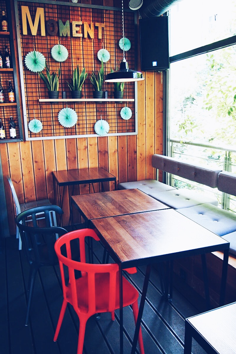 stoliki i napis Moment w restauracji Moment z grilla