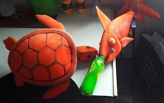 Uma tartaruga e um espadarte com uma garrafa presa no maxilar superior feitos de espuma cor de laranja pousados numa cadeira atrás do tapume.