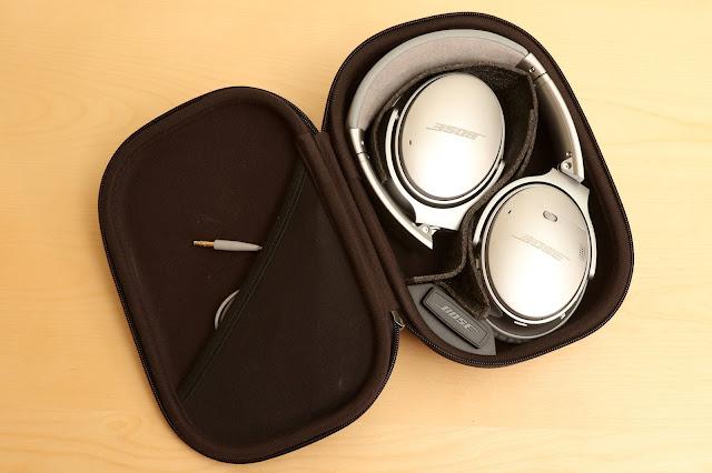 BOSE QuietComfort 35 攜行盒內部,可以看見左方的收納袋中有 2.5mm 轉 3.5mm  的音源線、USB  充電線、右方則是耳機本體,底下 BOSE logo 則是飛機上可用的 2  轉 1 轉接頭