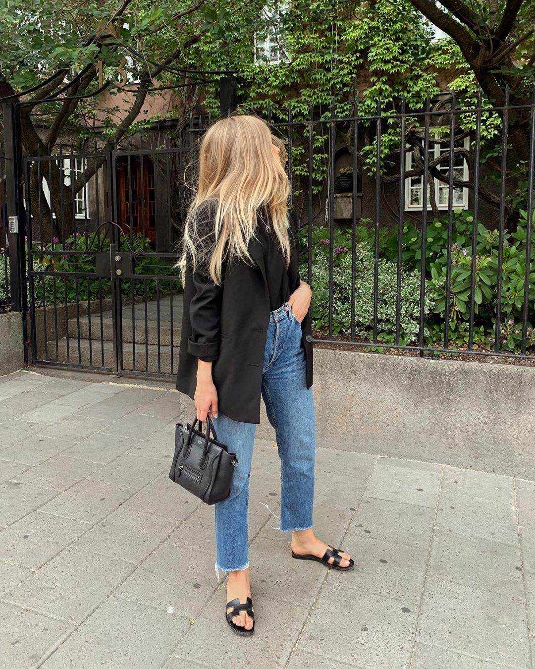 Easy Denim Spring Style Inspiration — black blazer, black t-shirt, black mini bag, high-waisted raw-hem jeans, and black flat sandals.