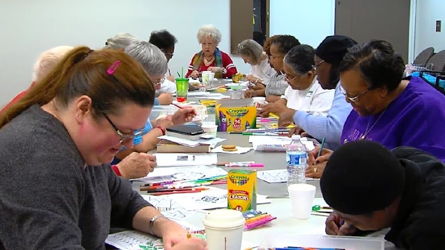 photo of adults coloring at library program; credit abc33/40.com