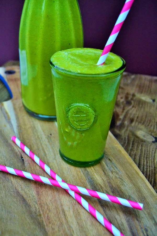 green smoothie in a tall glass with pink and white paper straws