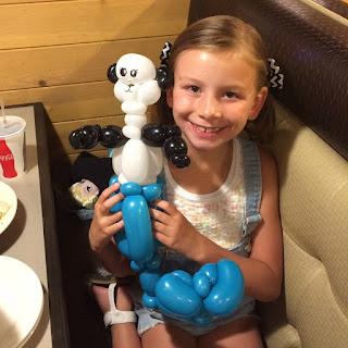 A Young Girl Holding a Half Panda Half Mermaid Balloon