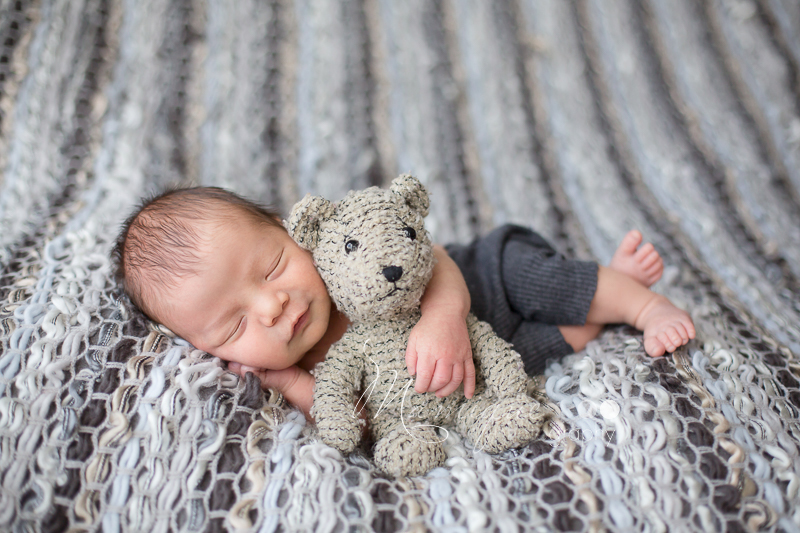 Newborn boy snuggling a teddy bear and smiling