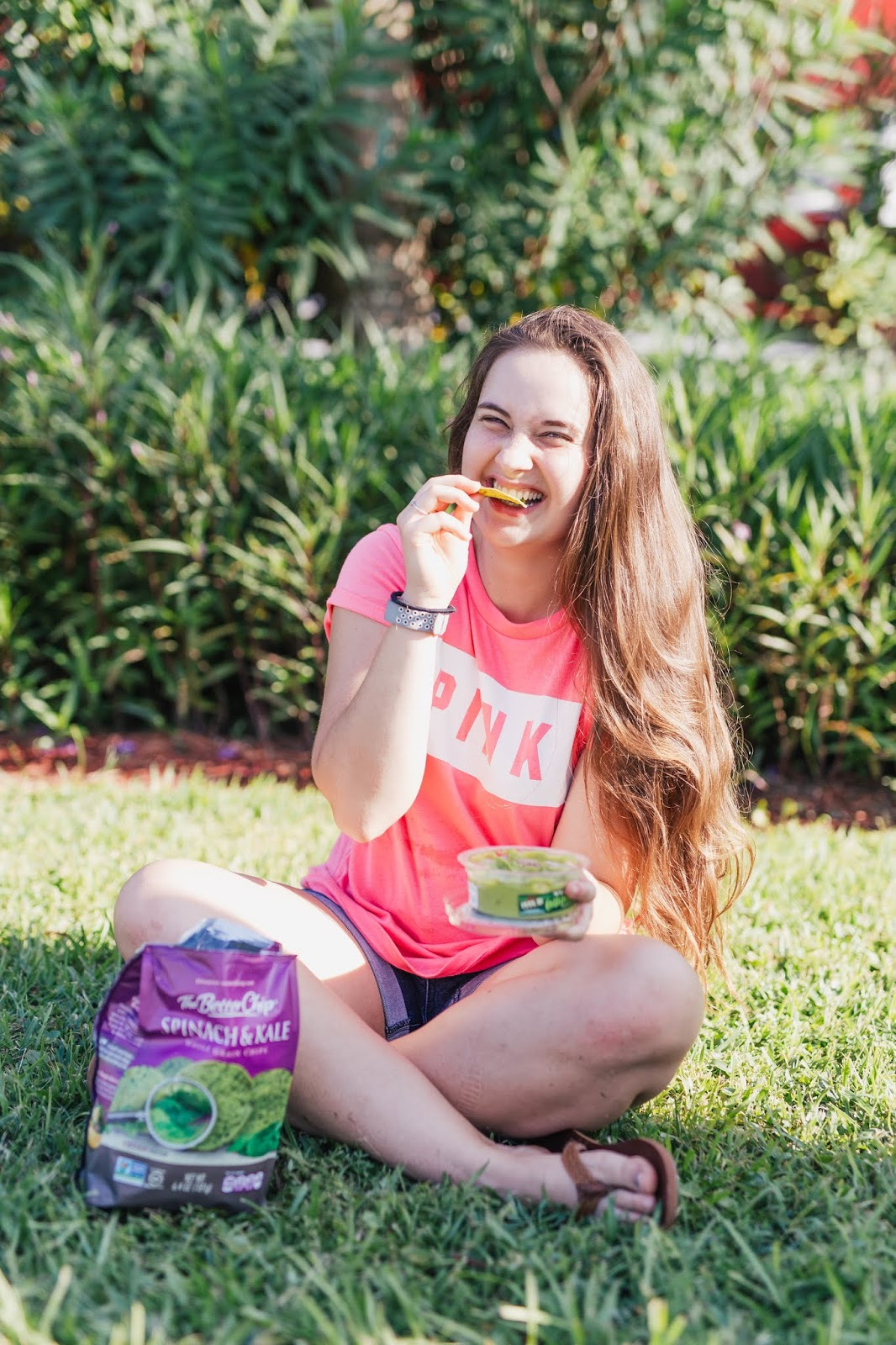 girl in victoria's secret pink tee holding the better chip spinach and kale chips and yucatan guacamole