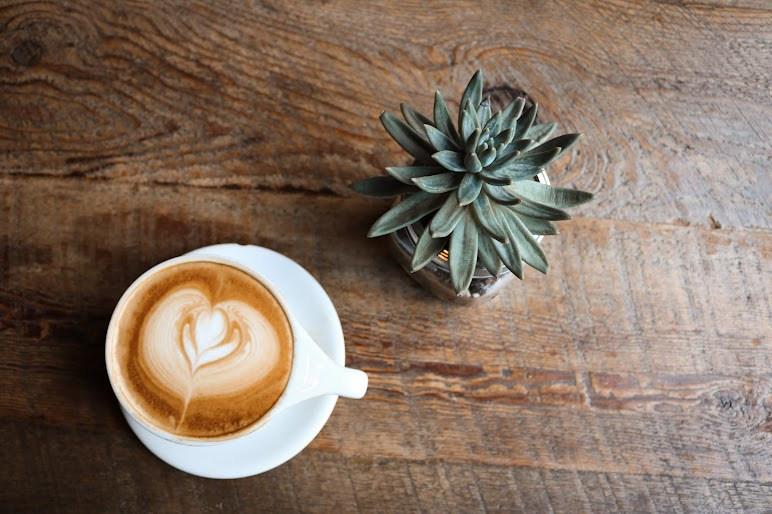 A Cup Of Coffee And Cactus On Wooden Table