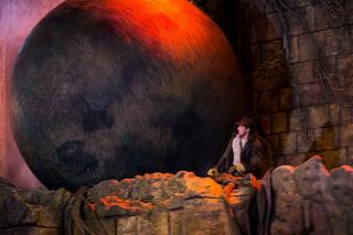 Hombre corriendo delate de una gran esfera de piedra