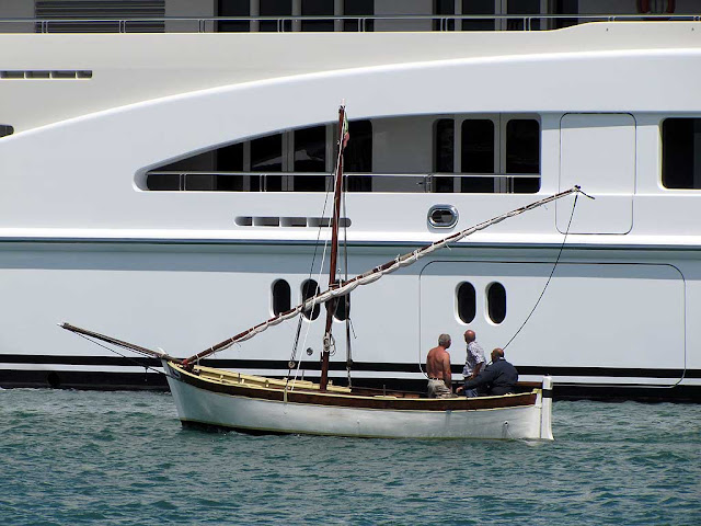 Three men in a boat looking at the superyacht Valerie, port of Livorno