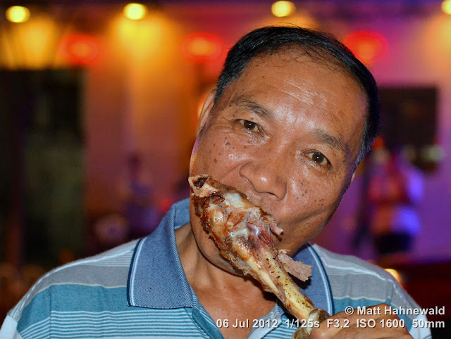 China, Beijing, Donghuamen night market, Chinese food delicacies, portrait, Chinese man eating leg of lamb