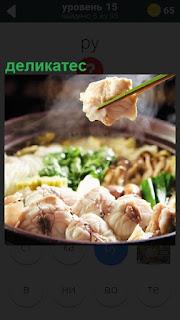 На сковородке приготовлено мясо деликатес и палочками взят один кусочек