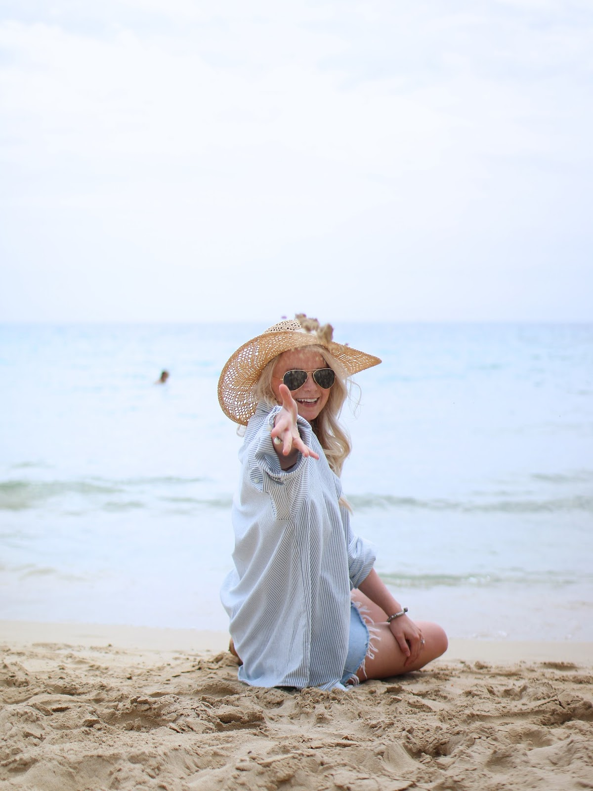 blonde wearing floppy sunhat on the beach throwing sand at the camera