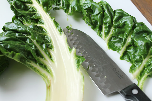 cutting leaves from stem of swiss chard with knife