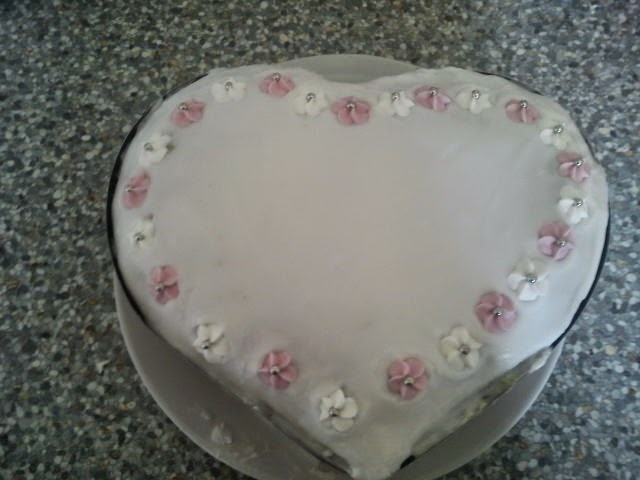 Pink iced heart-shaped cake, decorated with sugar flowers.
