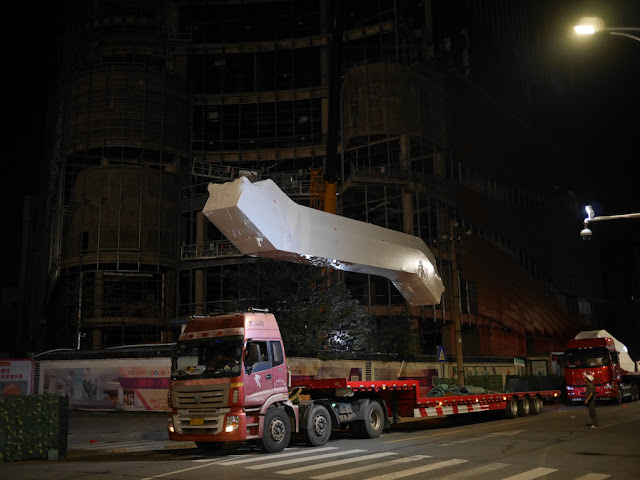 escalator hovering above a truck which delivered it to a construction site