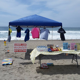 Open house layout of tables, canopies, brochures, signs, etc. on Zuma Beach for Aloha Beach Camp's Open House